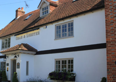 Luxury Self Catering - The Crab and Lobster Pub building on a sunny day, showing the front of a tiled roof pub