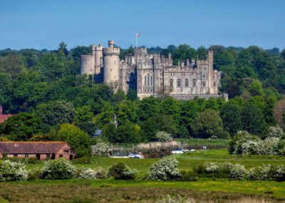 Luxury Self Catering - Arundel Castle taken from afar on a sunny day with fields and trees.