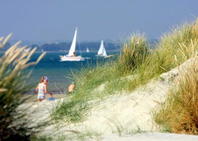 Luxury Self Catering - The Witterings beach, sand dunes, the sea in the background and and girl playing on the beach.